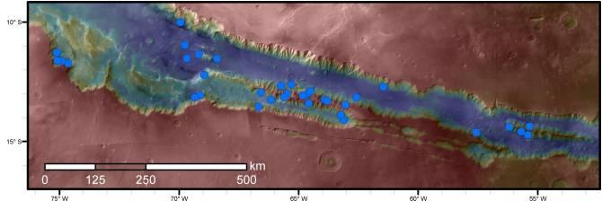 Los puntos azules en este mapa indican lugares de líneas recurrentes en pendientes, en una parte de la red de cañones de Valles Marineris en Marte. Estas líneas, oscuras y estacionales, podrían ser indicadoras de agua líquida. De entre todas las zonas de Marte cartografiadas, el área aquí mostrada tiene la densidad más alta de estas líneas. (Imagen: NASA/JPL-Caltech/Univ. of Arizona)